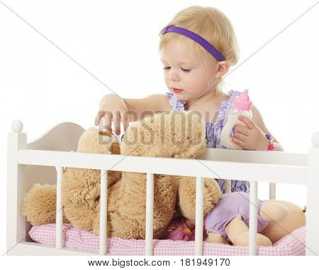 An adorable 2-year-old checking on the Teddy bear in her doll crib.  She holds a full baby bottle in one hand.  On a white background.