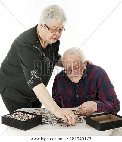 A senior couple (in their 80s), searching for the pieces of the jigsaw puzzle they're assembling.  On a white background.