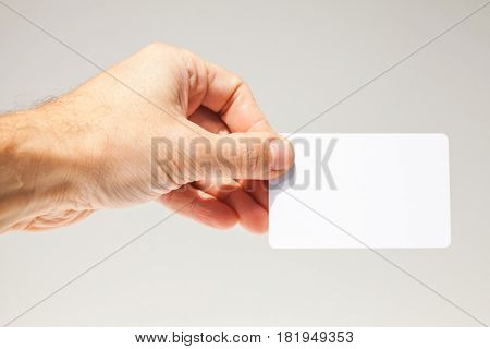 Male Hand With White Empty Card Over Gray