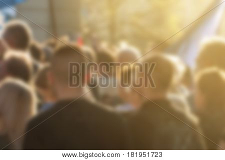 Large group of unrecognizable people as audience to politician's speech outdoors defocused crowd attending political meeting
