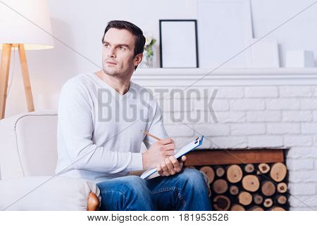Thoughtful look. Handsome thoughtful serious man sitting in the armchair and looking aside while holding his notes