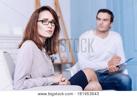 Psychological session. Beautiful nice unhappy woman sitting opposite her therapist and thinking about her problems while having a psychological session