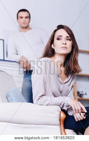 Overloaded with problems. Attractive cheerless young woman sitting in the armchair and holding her glasses while being overloaded with problems
