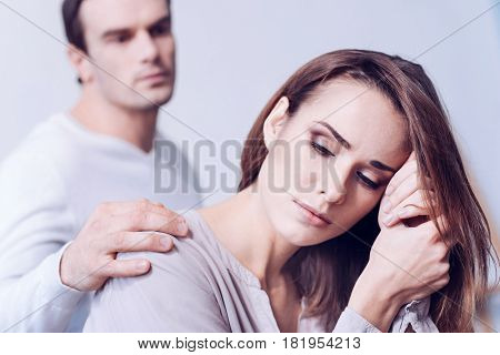 Do not be upset. Nice attractive handsome man putting his hand on the shoulder of his girlfriend and looking at her while supporting her