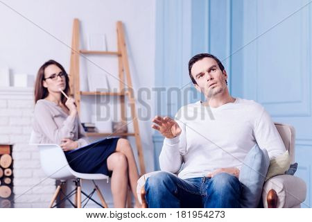 Visit to a therapist. Handsome unhappy nice man sitting in the armchair and telling about his problems while visiting a therapist