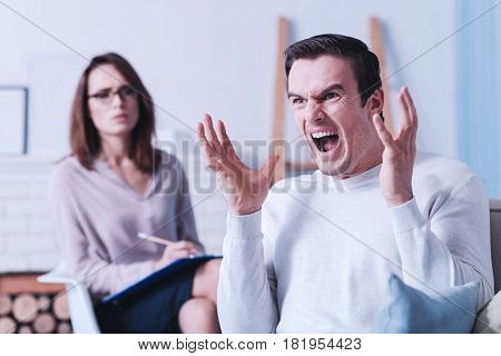 Being in despair. Angry furious emotional man crying and gesticulating while expressing his emotions