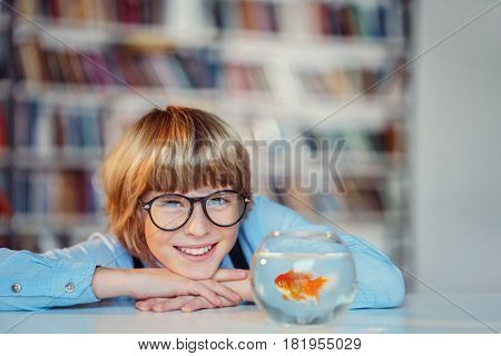 Smiling boy with goldfish in library