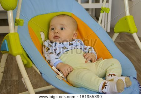 Little boy lying in the cradle and watching their parents
