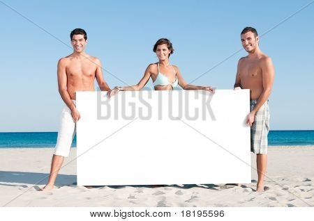 Happy smiling group of friends holding a white board for your text at summer beach