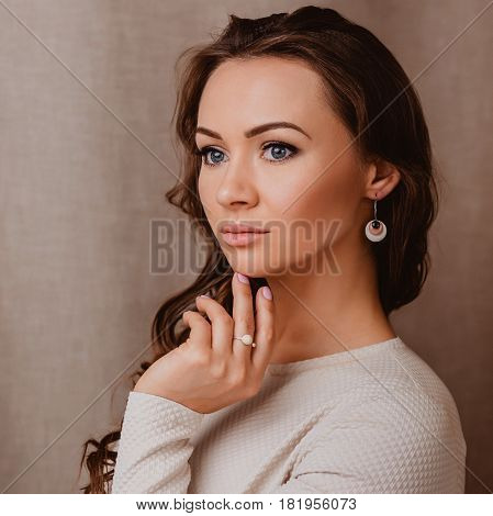 Fashion portrait of an attractive woman, turned half-profile, close-up face with perfect make-up