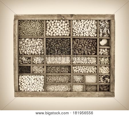 vintage, wooden typesetter case with variety of beans, lentils, peas, grains and seeds, black and white platinum toned image