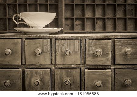 classic tea cup on top of rustic apothecary drawer cabinet, black and white platinum toned