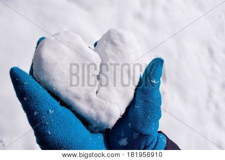 A man in blue gloves holds snow in his arms in the form of a heart. It is broken into two parts. Symbol of parting and breaking.