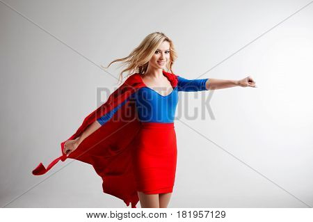 Superhero Woman. Young and beautiful blonde in the image of a super heroine in a red Cape blowing
