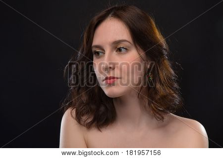 Portrait of brunette woman with nude shoulders on black background