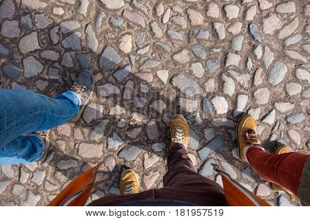 Three Friends Walk In Shoes Along The Pavement. Walk In The Fresh Air