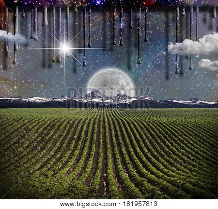 Surrealism. Field with green rows. Giant moon rises over the mountains. Another dimension flows down.     Some elements provided courtesy of NASA