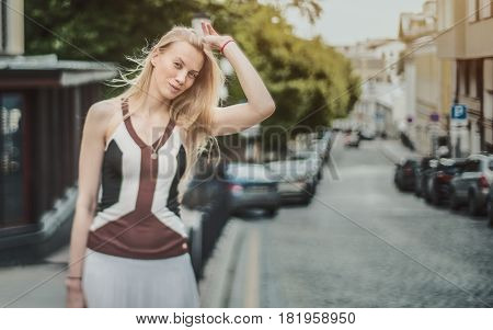 True tilt-shift shooting: charming adult caucasian blonde woman with fluttering long hair standing on street during warm spring day with copy space for your advertising message or promotional content