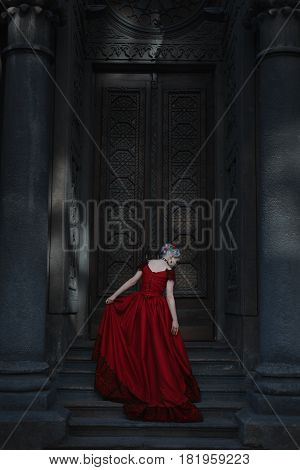 Woman steps on the steps of a fairytale castle.