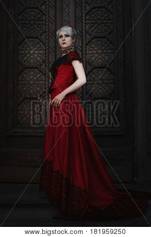 Woman in a red ball gown she stands in front of a fairy-tale door to the castle.