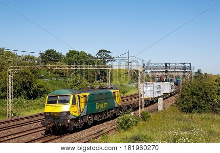 LINSLADE, UK - JUNE 30: A Freightliner operated intermodal freight train approaches Linslade tunnels on route to Felixstowe docks on June 30, 2015 in Linslade. FLT employ approx 2,500 personnel