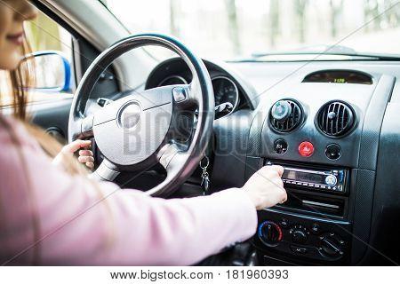 Woman Set Up Music In Car. Car Dashboard. Radio Closeup. Woman Sets Up Radio