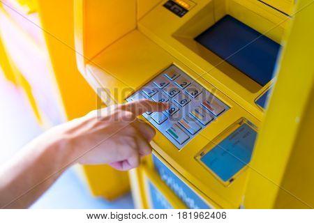 Man hand entering his PIN at an ATM