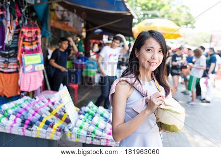 Woman having coconut drink in street market