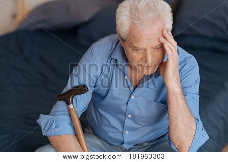 So many memories. Unhappy sad aged man sitting on the bed and touching his head while thinking about his past