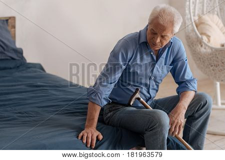 Empty space. Unhappy cheerless elderly man sitting on the bed and putting his hand on the empty space near him while feeling lonely