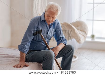 Feeling of loneliness. Unhappy moody aged man holding a walking stick and looking at the empty space near him while sitting on the bed