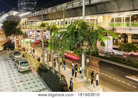Main Road Sukhumvit With People And Traffic In Bangkok By Night With Sky Train Station