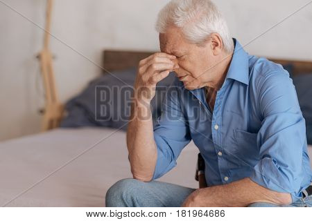 Period of depression. Moody grey haired aged man sitting on the bed and holding his nasal bridge while being in depression