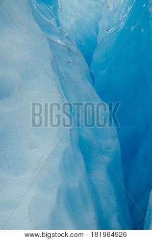 Blue colors of ice inside glacier abstract background
