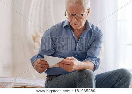 Old memories. Moody cheerless aged man holding an old letter and reading it while being nostalgic about his past