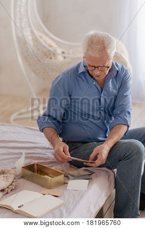 My memories. Pleasant sad senior man turning over old letters and remembering his past while sitting on the bed