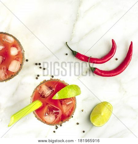 Bloody Mary cocktails, shot from above on a white marble texture, with red hot chili peppers, slices of lime, celery sticks, a piece of tomato and copyspace, square photo