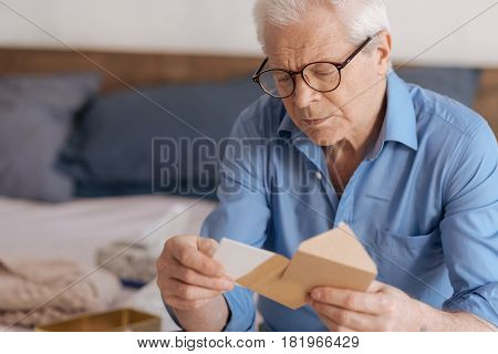 Long forgotten words. Gloomy cheerless aged man holding an envelope and taking out a note while intending to read it