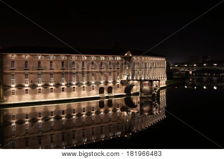 Garrone River night scenes of Toulouse architecture illuminated historic building now Hotel-Dieu Saint Jacques reflected in river in distance and reflected in calm water.