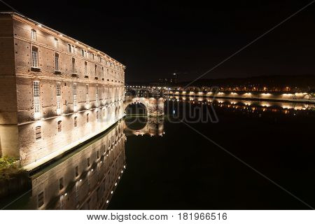 Garrone River night scenes of Toulouse architecture historic building now Hotel-Dieu Saint Jacques reflected in river Saint Peirre Bridge illuminated in distance and reflected in calm water.