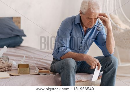 Nostalgic feelings. Thoughtful depressed unhappy man holding a letter and touching his head while being involved in his memories