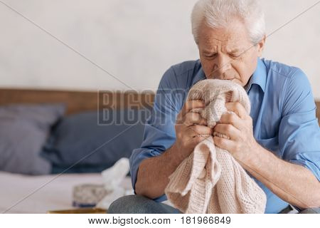 Great loss. Cheerless depressed aged man holding his deceased wifes knitted jacket and remembering about her while being in grief