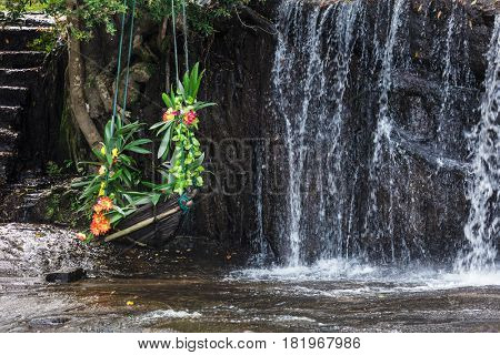 swing with flowers and stairs to a beautiful waterfall