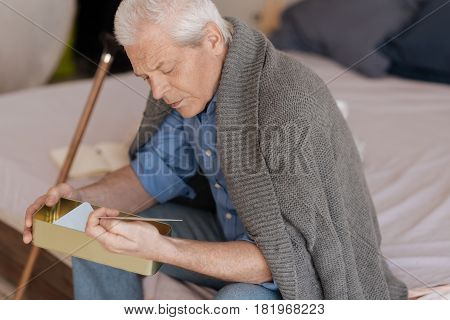 Reminiscent of the old days. Sad depressed unhappy man holding a box and looking at the photo while taking it out