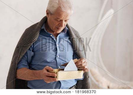 Happy memories. Thoughtful nice aged man looking at the box with letters and holding an envelope while remembering his past