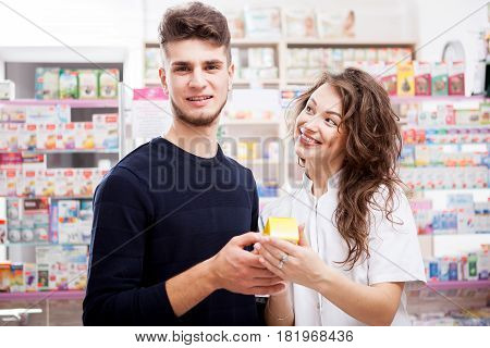 Pharmacist woman and client in front of the shop. Healthcare business