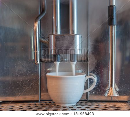 Foaming milk process from coffee machine pouring to white hot coffee cup.
