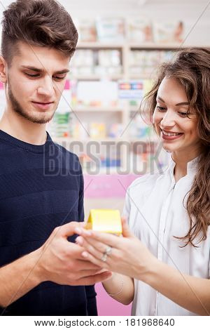 Pharmacist woman and her client looking at a box with pills. Healthcare business
