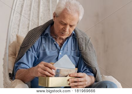 Enough for today. Moody cheerless sad man holding a box and putting his letters into is while sitting in the armchair
