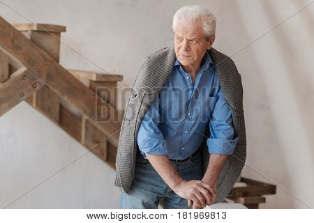 Thoughtful look. Unhappy grey haired elderly man standing in the room and leaning on the walking stick while looking aside